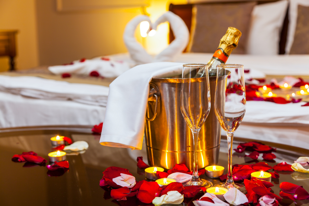 Romantic hotel room getaway, a table with a fruit plate and candles, in the background a bed decorated with swans of towels and rose petals